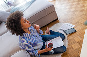 Wine brings fresh ideas. Beautiful young woman holding a glass of wine and using tablet while sitting on the floor at home. Relaxing work at home: concept with a girl sitting on the floor