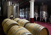 wine cellar with  wooden and stell barrels   in contemporary winemaker factory