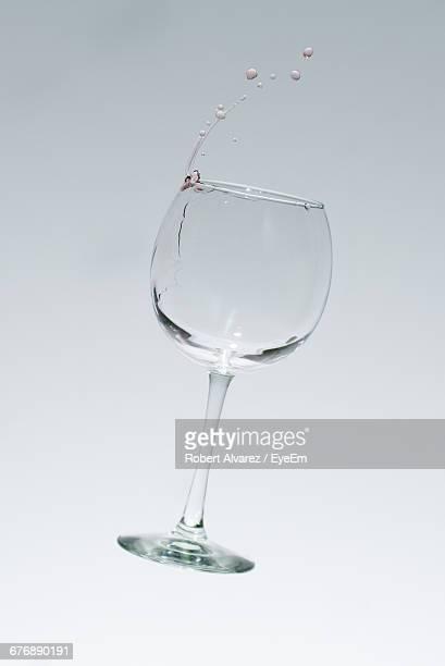 Wine Falling From Glass Against White Background