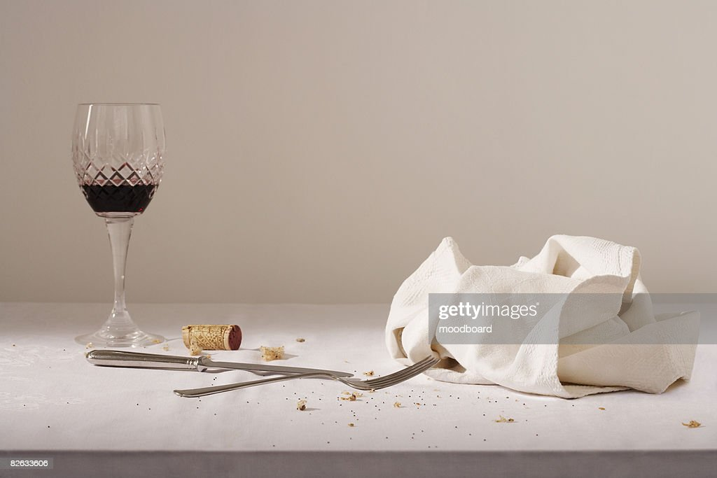 Wine glass, cutlery, dish cloth on messy table : Stock Photo