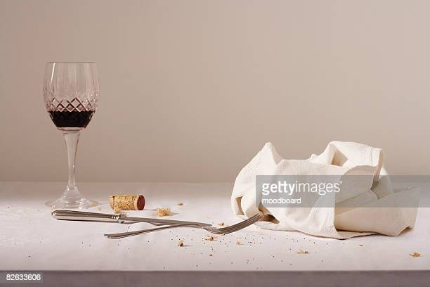 Wine glass, cutlery, dish cloth on messy table