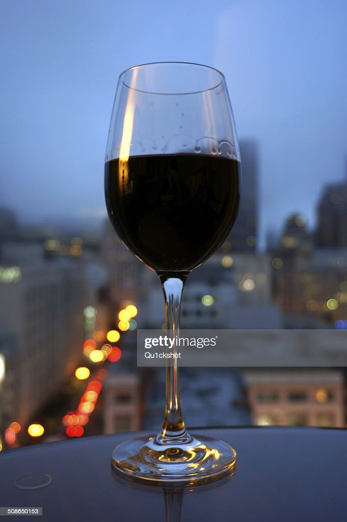 Wine glass on table in front of city : Stock Photo