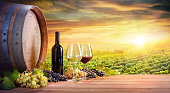 Red And White Wineglasses With Old Barrel And Botte And Grapes In Vineyard At Dust