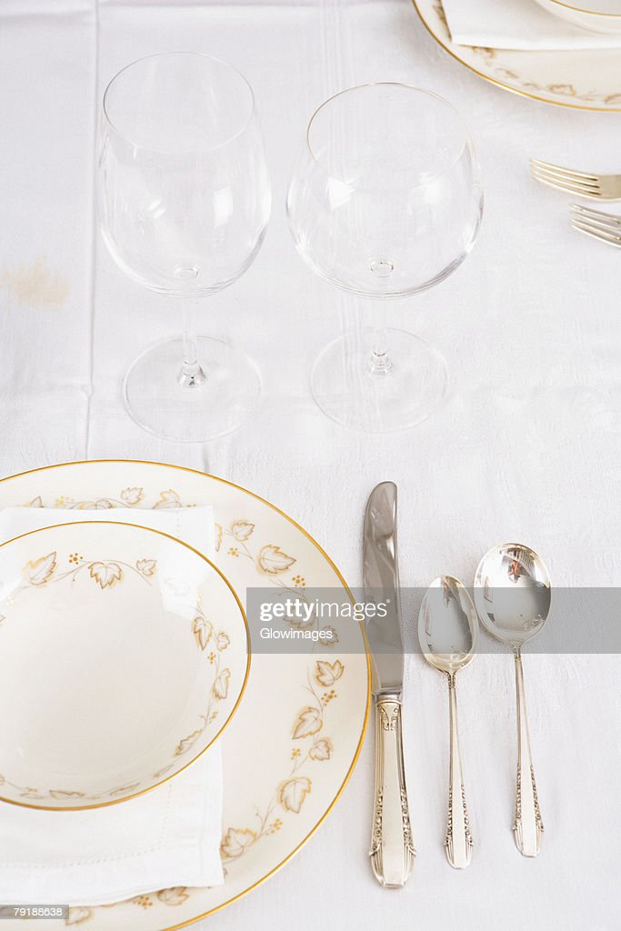 Wine glasses with plates and cutleries on a dining table : Stock Photo