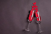 a pair of champagne glasses with red hearts on gray background, concept of love, saint valentine day