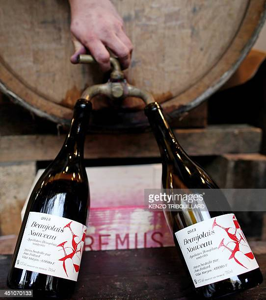 A wine grower bottles some 2013 'Beaujolais Nouveau' wine on November 21 2013 in Paris From the heart of France to the foothills of Mount Fuji and...