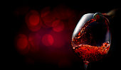 Wine pouring into wineglass on dark red background