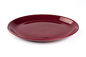 Pastel wine red colored plate isolated on white background, front view, clipping path, excluding the cast shadow, included.