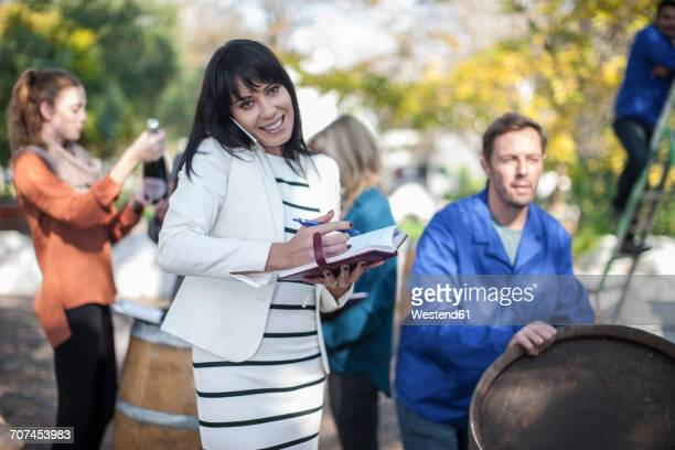 Wine saleswoman with group of clients outdoors and wine worker with barrel
