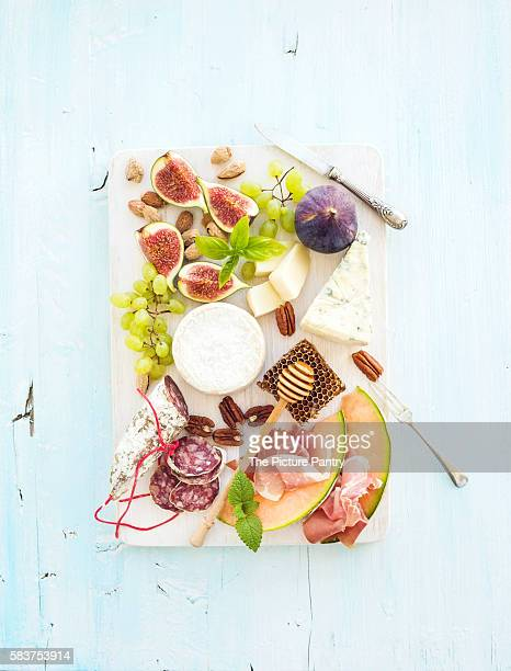 Wine snack set. Figs, grapes, nuts, cheese variety, meat appetizers and herbs on light blue background, top view.