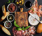 Wine snack set with empty wooden board in center. Glass of red, meat selection, mediterranean olives, sun-dried tomatoes, baguette slices, camembert cheese and spices on black background, top view, co