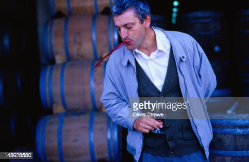 Wine taster from Bodegar ( winery ) de Sarria spitting out red wine - Puente de la Reina, Navarra