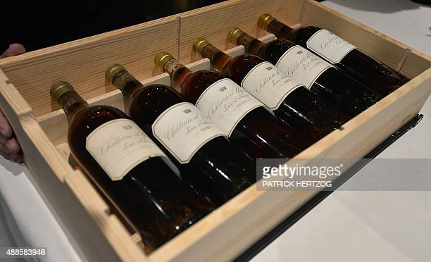 A wine waiter displays bottles of famous Sauternes wine 'Chateau Yquem' over 100years old in the wine cellar of the restaurant Villa Lalique in...