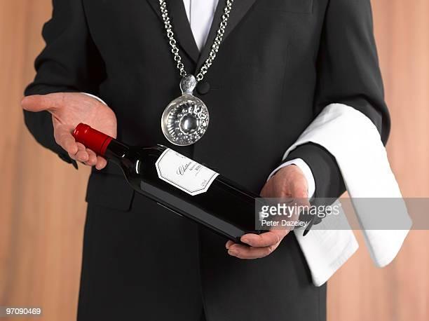 Wine waiter sommelier presenting bottle of wine
