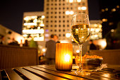 Glass of white wine and candle with evening view of city buildings