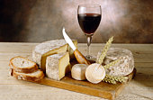 Wine with cheeses and breads on cutting board