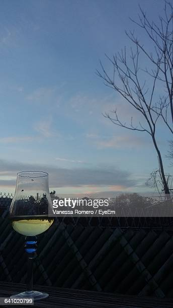 Wineglass On Table Against Sky During Sunset