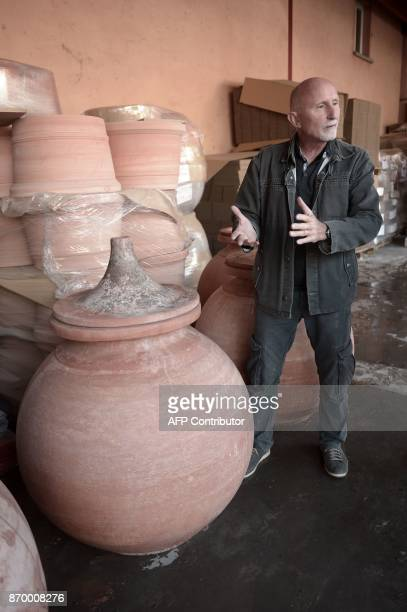 Winemaker in Bergerac Luc de Conti explains the benefits of aging wine in 'dolia' earthenware jars on October 12 at the Goicoechea potters' workshop...