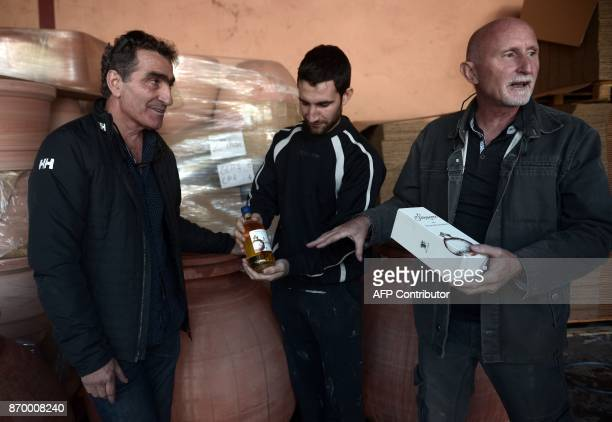 Winemaker in Bergerac Luc de Conti shows his first vintage aged in 'dolia' earthenware jars flanked by winmaker Michel Riouspeyrous and potter Inaki...