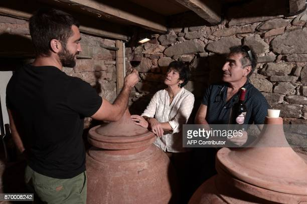 Winemakers Iban Therese and Michel Riouspeyrous taste wine aged in 'dolia' earthenware jars on October 12 in Irouleguy southwestern France The...