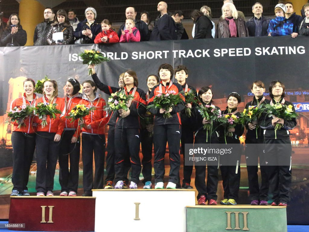 Winers Team China (C), second palced Team Canada (L), third placed Team Japan pose after women's 3000m relay at the 2013 ISU Short Track Speed Skating World Championships, on March 10, 2013 in Debrecen, Hungary.