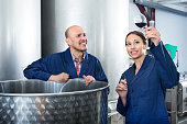 Two cheerful winery workers holding glass of wine in the fermenting section of factory. Focus on both persons