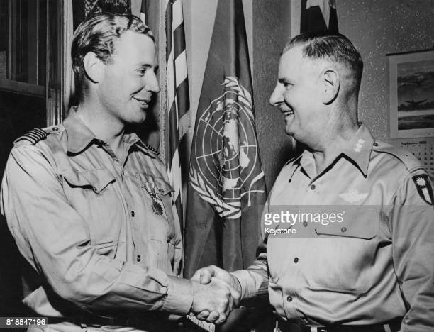 Wing Commander Peter WykehamBarnes of the RAF a wartime flying ace receives an American Air Medal from Lieutenant General George Stratemeyer...
