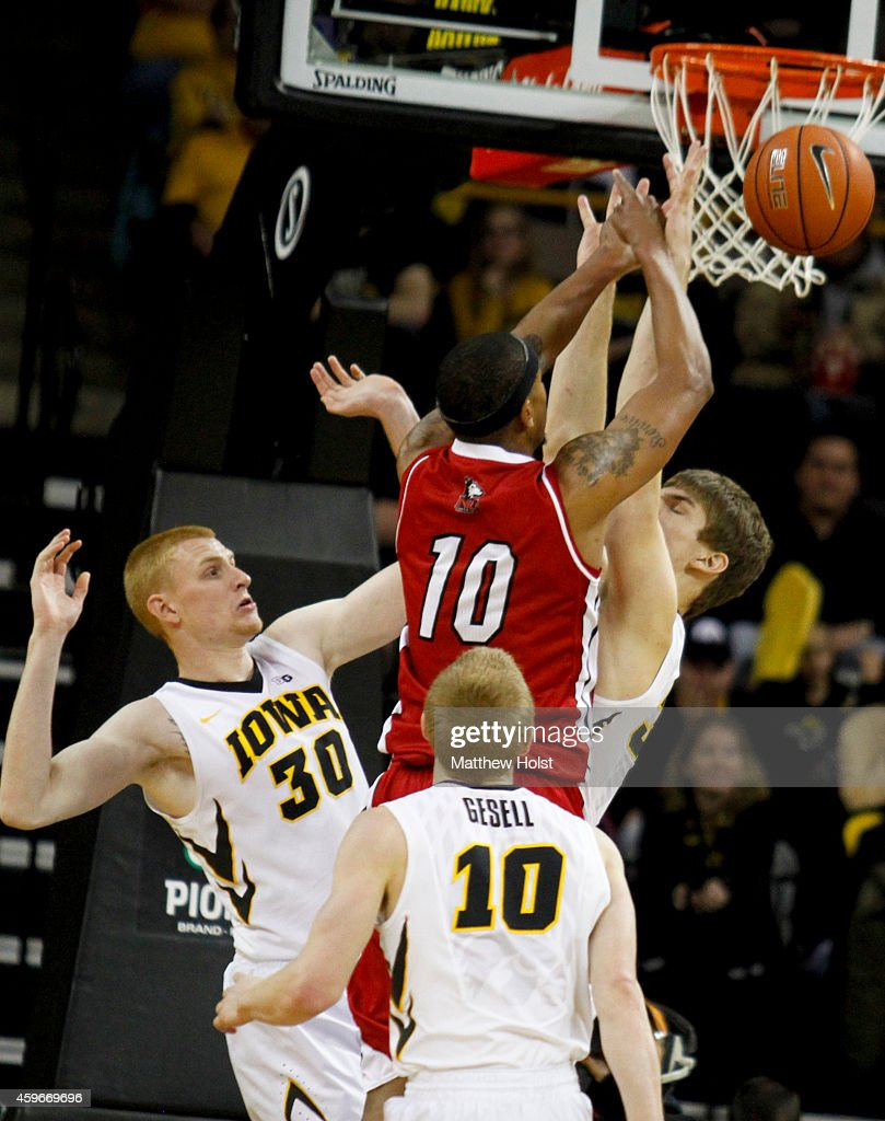 Wing Darrell Bowie #10 of the Northern Illinois Huskies goes to the basket against center Adam Woodbury #34, forward <a gi-track='captionPersonalityLinkClicked' href=/galleries/search?phrase=Aaron+White+-+Basketball+Player&family=editorial&specificpeople=14619648 ng-click='$event.stopPropagation()'>Aaron White</a> #30 and guard Mike Gesell #10 of the Iowa Hawkeyes, in the first half on November 26, 2014 at Carver-Hawkeye Arena, in Iowa City, Iowa.