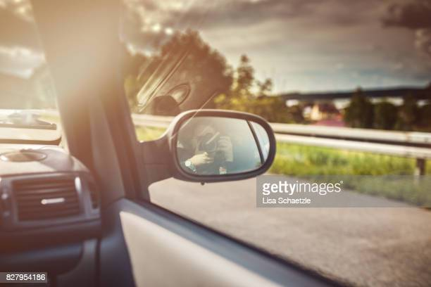 Wing mirror with mirror image of woman taking picture of herself in a driving car