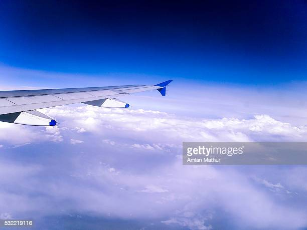 Wing of a plane flying among the clouds with blue sky