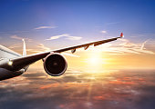 Detail of wing of commercial jet airplane flying above clouds in beautiful sunset light. Front view. Air travel and vacation concept.