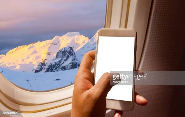 Wing of airplane near window seat and wing with Alps mountain range