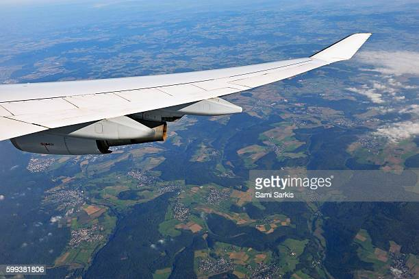 Wing of flying airplane over Germany, Europe - with tiny German villages below