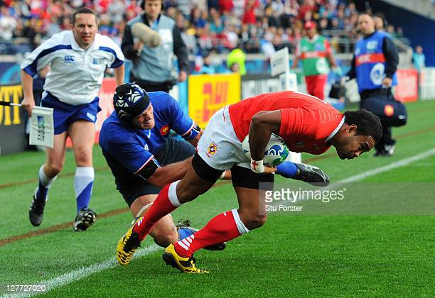 Wing Sukanaivalu Hufanga of Tonga breaks through the challenge from Julien Bonnaire of France to score the opening try during the IRB 2011 Rugby...