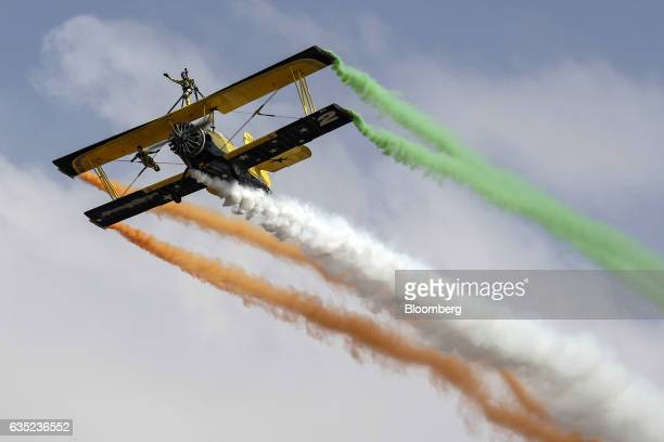 Wing walkers perform stunts on the wings of a biplane during an aerial flying display at the Aero India air show at Air Force Station Yelahanka in...
