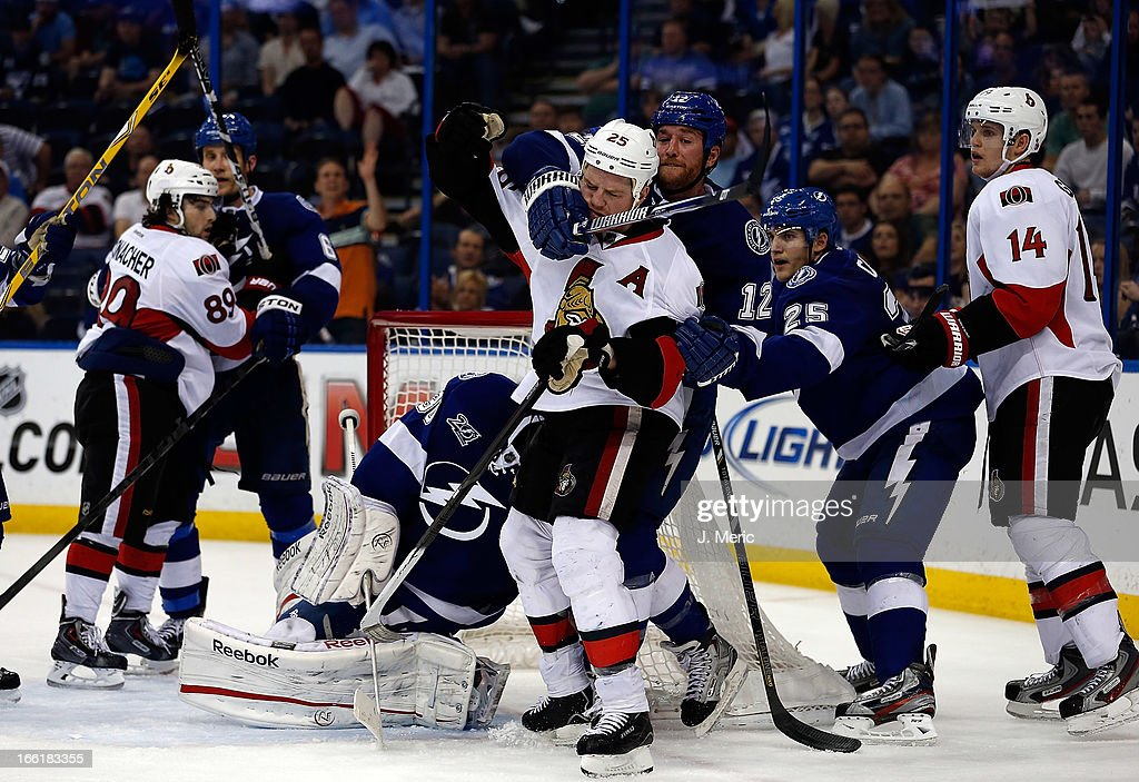 Winger Ryan Malone #12 of the Tampa Bay Lightning ties up winger Chris Neil #25 of the Ottawa Senators during the game at the Tampa Bay Times Forum on April 9, 2013 in Tampa, Florida.