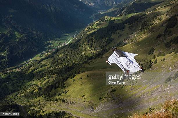 Wingsuit BASE jumper is flying down a mountain