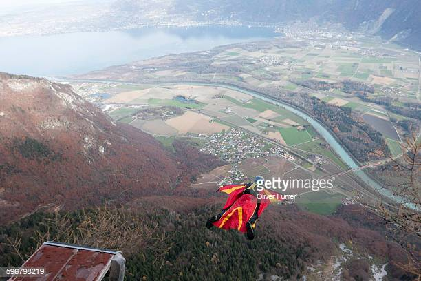 Wingsuit BASE jumper is flying down the mountain