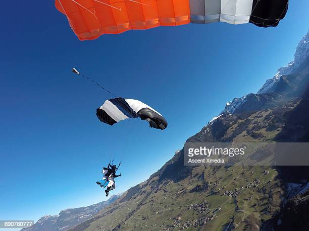 Wingsuit flier descends into mountain landscape