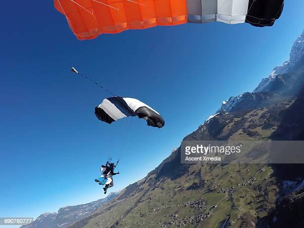 Wingsuit flier descends into mountain landscape