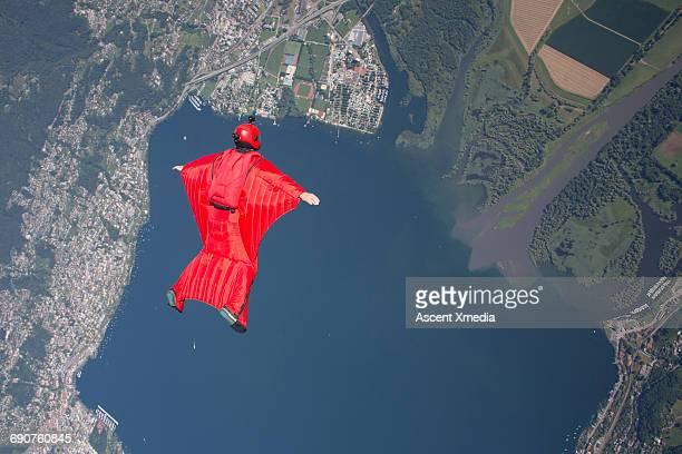 Wingsuit flier glides above lake, village
