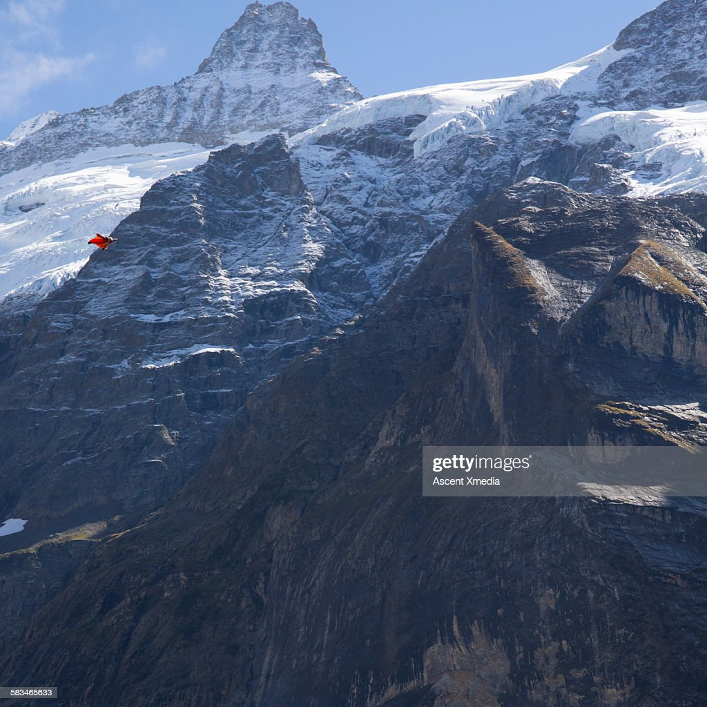 Wingsuit flier in airborne descent over mountains