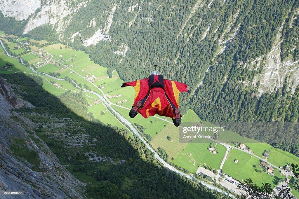 Wingsuit flier in airborne descent towards valley