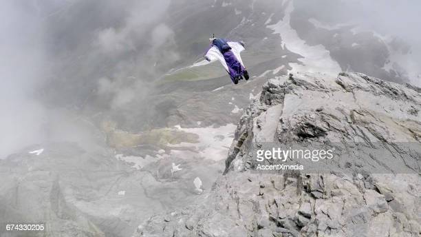 Wingsuit flier in midair, over mountain landscape