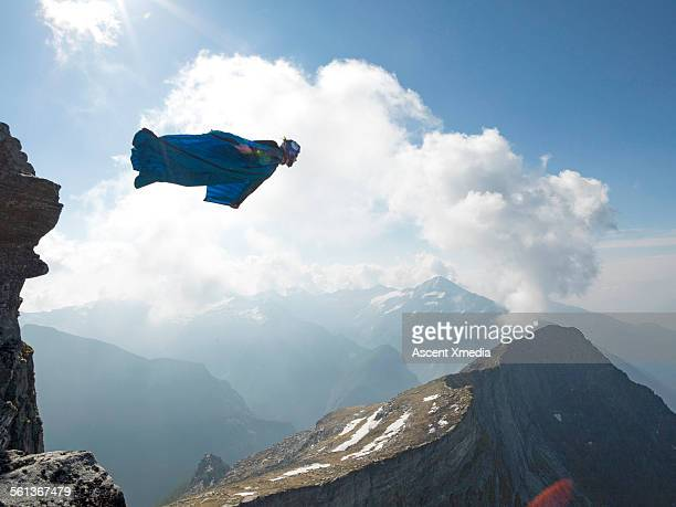 Wingsuit flier launches at cliff edge, above mtns