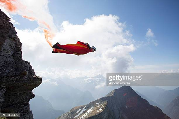 Wingsuit flier launches at cliff edge, smoke trail