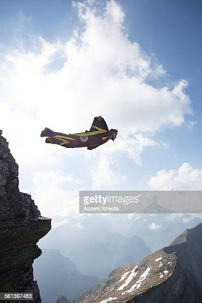 Wingsuit flier launches from cliff edge, in mtns