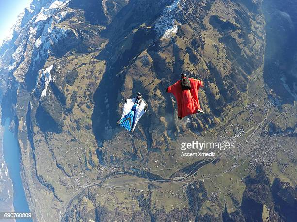 Wingsuit fliers glide above mountain landscape