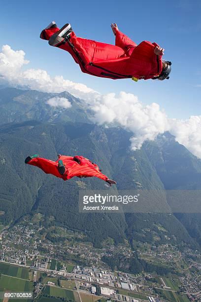 Wingsuit fliers glide above mountain landscape