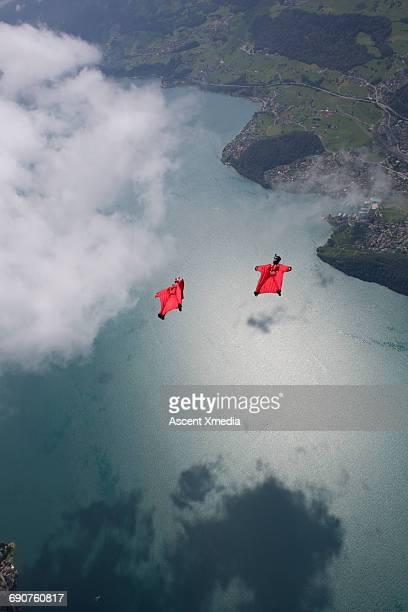 Wingsuit fliers glide above village, lake